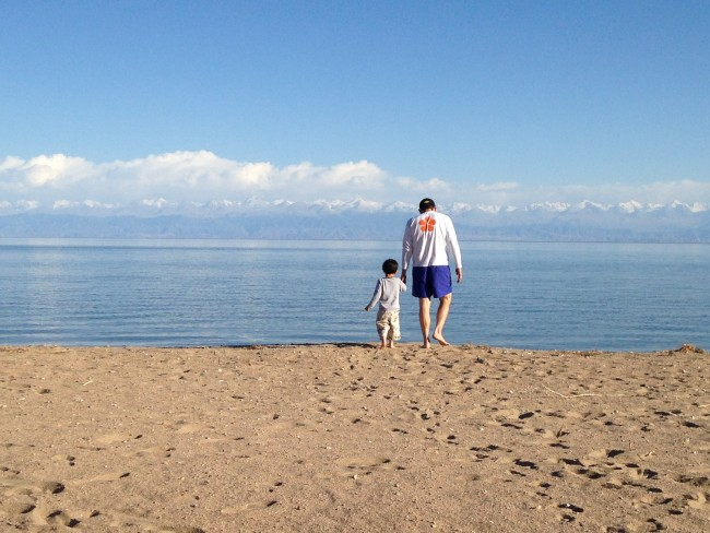 photo of a man and a boy on a beach looking out at the water
